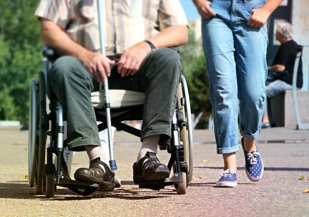車椅子の男性と散歩する画像
